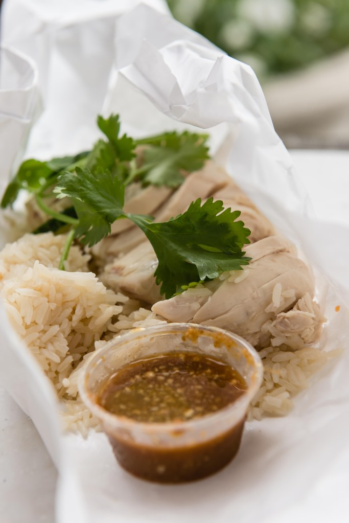 Nong's Khao Man Gai 1003 SW Alder Street Pictured:  Khao Man Gai (Chicken and Rice) Nong's Khao Man Gai only serves one dish:  chicken and rice. And now I understand why. This is a Thai version of Hainanese chicken and rice, or what we call cơm gà Hải Nam. The chicken and rice is packaged up in a small paper bundle and comes with the most incredible dipping sauce. This sauce is so good they've bottled it and sell it in select Portland stores as well as online.